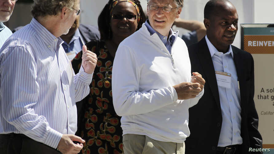 """FILE - Bill Gates (R) and former Microsoft chief technology officer and co-founder of Intellectual Ventures Nathan Myhrvold (L) speak while reviewing the displays at the """"Reinvent the Toilet Fair"""" competition at the Bill and Melinda Gates Foundation"""