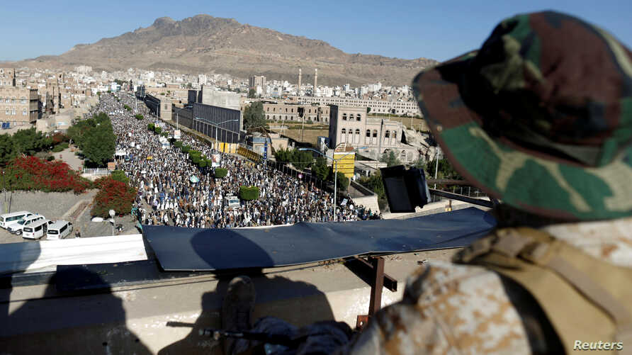 A Houthi militant sits guard on the roof of a building overlooking fellow Houthis rallying to denounce the rapid devaluation of the Yemeni Rial in Sanaa, Yemen, Oct. 5, 2018.