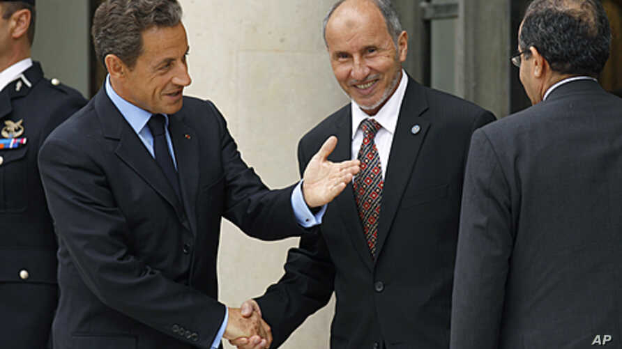 """France's President Nicolas Sarkozy (L) welcomes Mustafa Abdel Jalil (C), chairman of the Libyan National Transitional Council (NTC), and Mahmoud Jibril (R), the head of Libya's rebel National Transitional Council, prior to the opening of the """"Friends"""