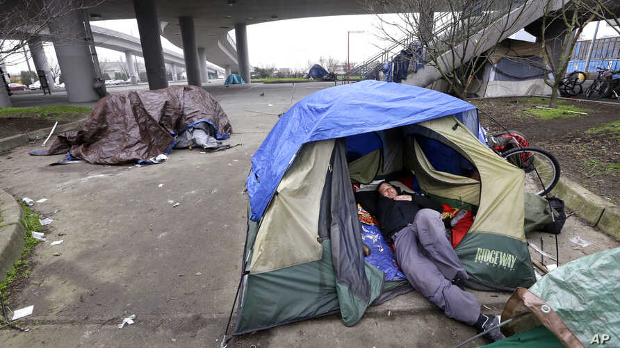 FILE - A man lies in a tent with others camped nearby, under and near an overpass in Seattle, Feb. 9, 2016. Microsoft pledged $500 million to address homelessness and develop affordable housing in response to the Seattle region's widening affordabili
