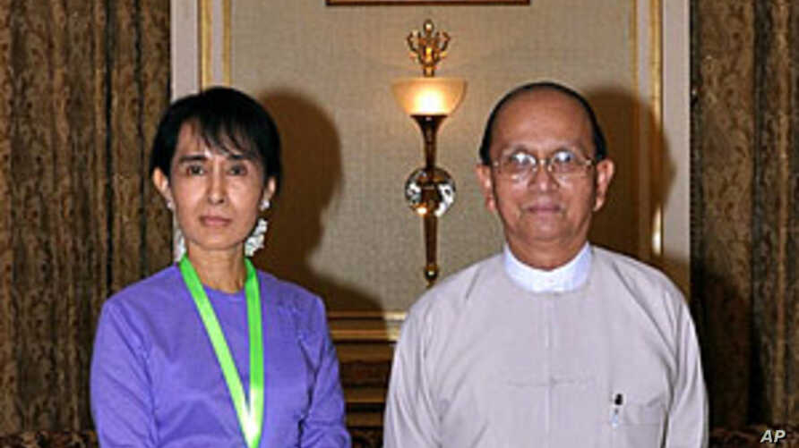 Burma's democracy icon Aung San Suu Kyi and President Thein Sein pose for photos before their meeting at the presidential office in Naypyidaw, August 19, 2011