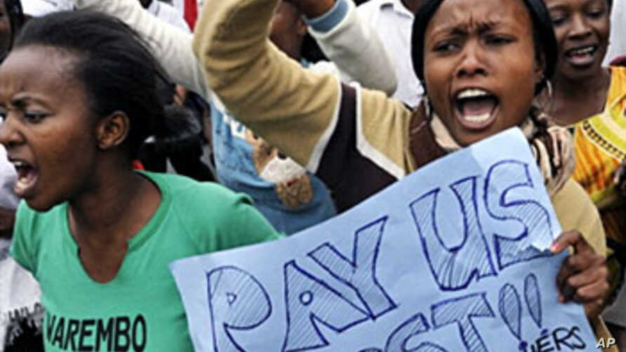 """Protesters march in the streets of Nairobi, holding a placard that reads """"Pay us first!! Teachers-Police-IDPs"""" 08 Jul 2010"""