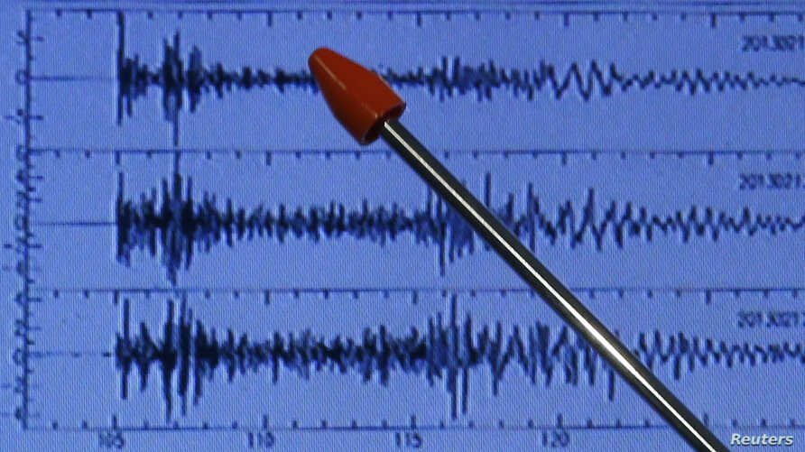 Official of Japan's earthquake agency points at graph of ground motion waveform data observed Feb. 12, 2013 from North Korean nuclear test