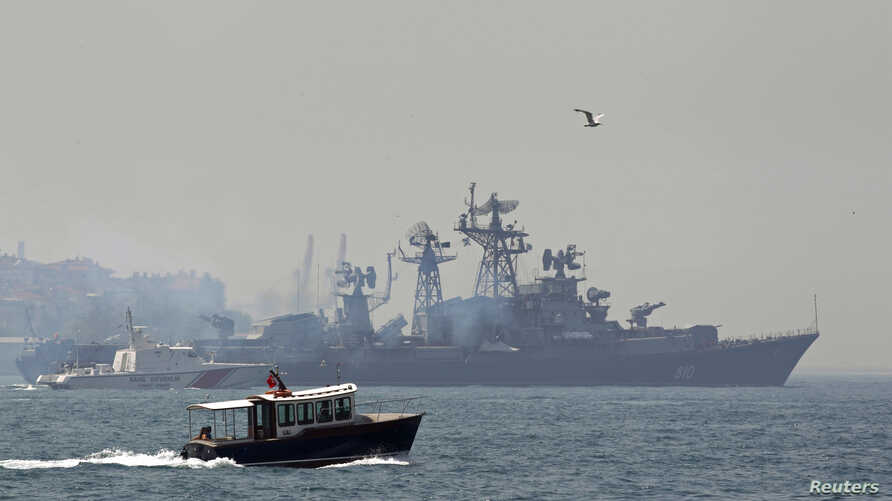 A Turkish Navy cost guard boat (L) escorts the Russian Navy destroyer Smetlivy, in the Bosphorus in Istanbul, July 11, 2012.