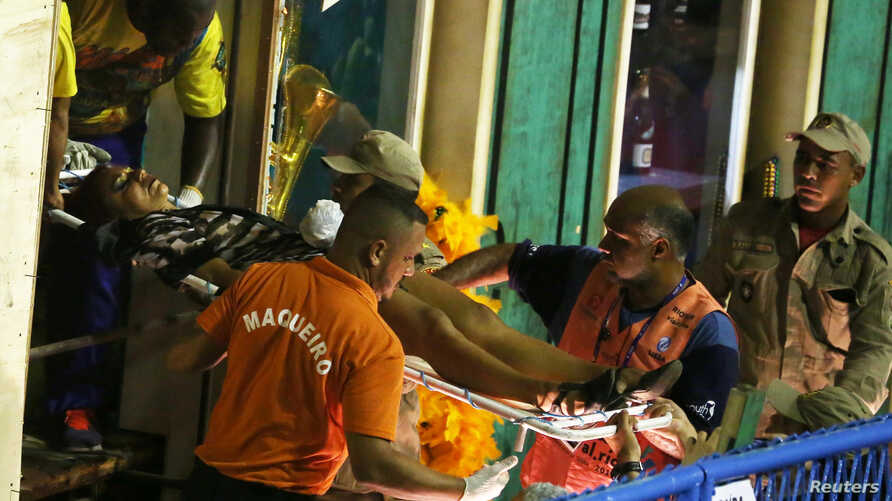 A reveler is assisted after an accident with a float from Unidos da Tijuca samba school during the second night of the carnival parade at the Sambadrome in Rio de Janeiro, Brazil, Feb. 28, 2017.