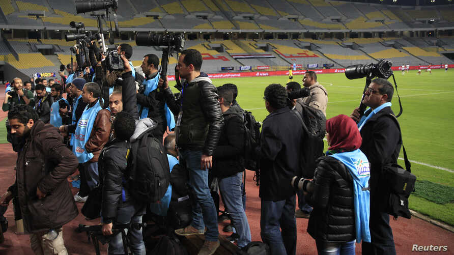 """Egyptian photojournalists hold their cameras during a silent protest against preventing them by the officials from covering the Egyptian Premier League derby soccer match between Al-Ahly and El Zamalek at Borg El Arab """"Army Stadium"""", west of Alexandr"""