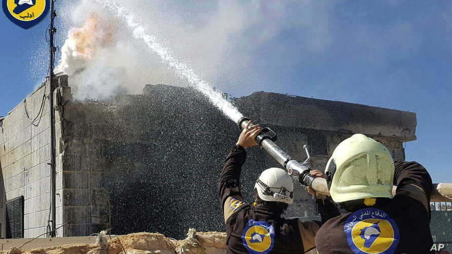 This photo provided by the Syrian Civil Defense group known as the White Helmets, shows Civil Defense workers putting out a fire in a house following airstrikes hit Maarat al-Nuaman town, in Idlib province, Syria, March 25, 2017.