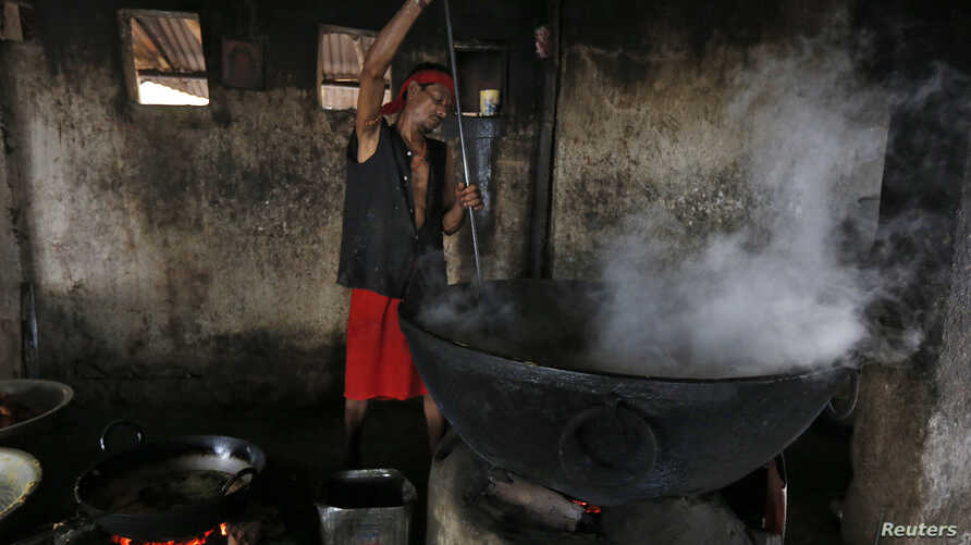 FILE - A man prepares food inside a community kitchen at a Hindu temple on the banks of the river Ganges in Kolkata, India, May 5, 2016. Forty students were hospitalized after consuming lunch in India's northwestern Rajasthan state Friday.