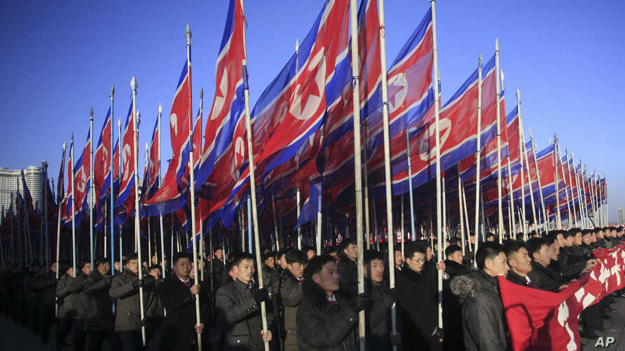 North Koreans parade with the North Korean flag in Kim Il Sung Square in Pyongyang to show their loyalty to the Workers' Party, Feb. 25, 2016.