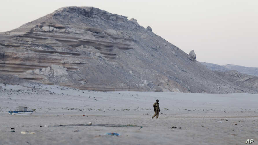 FILE - A Somali government soldier walks in Eyl, in Somalia's northeastern region of Puntland. U.S. airstrikes reportedly targeted members of a pro-Islamic State militants group in a remote mountainous part of the region.