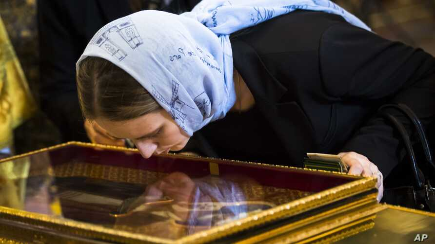 In this photo taken May 26, 2017, an Orthodox believer kisses the relics of Saint Nicholas that were brought from an Italian church where they have lain for 930 years, in the Christ the Savior Cathedral in Moscow, Russia.