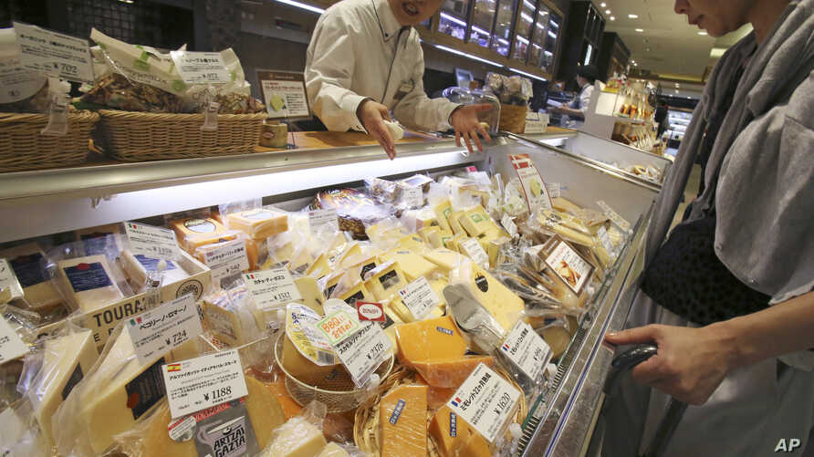 A customer looks at various types of imported cheese sold at a department store in Tokyo in this July 1, 2017, photo.