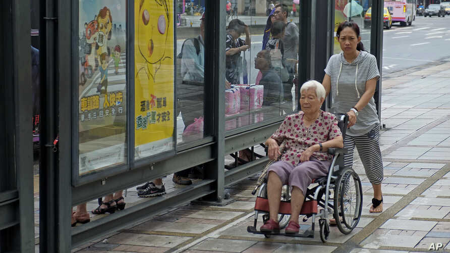 FILE - Caregiver pushes elderly wheelchair-bound woman through Taipei, Taiwan, Sept. 30, 2013.