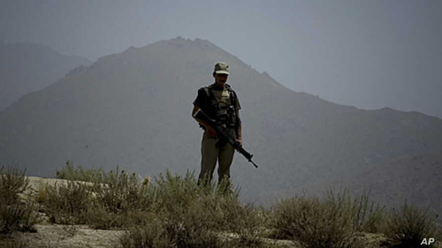 A Pakistani army soldier stands guards on a hilltop post in Hadambar, in Pakistan's Mohmand tribal region along the Afghan border, June 1, 2011.