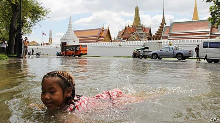A girl swims in the floodwater in front of Bangkok's Grand Palace in a riverside neighborhood, Thailand.