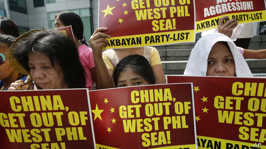 Protesters picket the Chinese Consulate at the financial district of Makati city east of Manila, Philippines, March 3, 2014, to protest the recent use of water cannons by Chinese coast guard to drive away Filipino fishermen off the disputed Scarborou