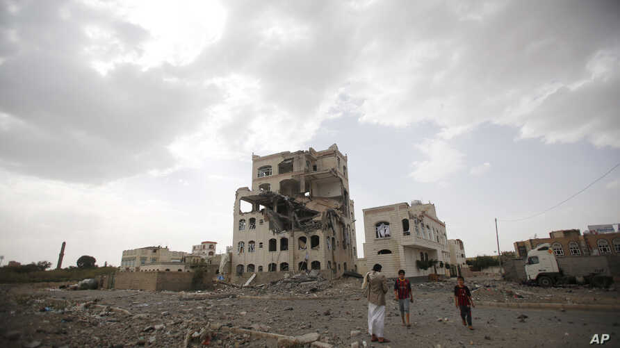 People stand by a building destroyed by a Saudi-led airstrike in Sana'a, Yemen, July 6, 2015.