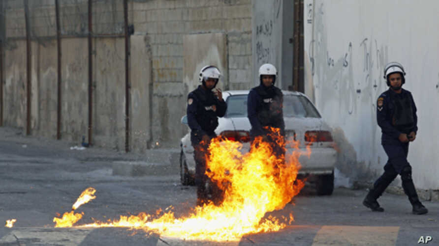 Riot police step back as a Molotov cocktail fired by anti-government protesters explodes during clashes in the village of Sanabis, west of Manama, Bahrain, February 12, 2012.