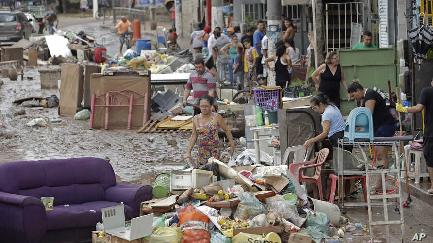 Damaged belongings, spoiled food and soaked furniture are piled up in the street to be taken away as trash after flooding in Sao Paulo, Brazil, March 11, 2019.