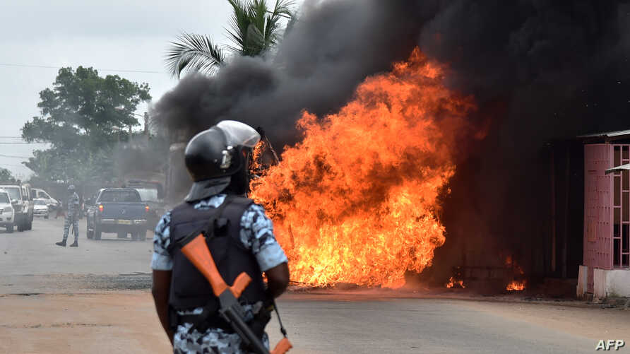An Ivorian police officer stands near a burning bus in Abidjan, Sept. 10, 2015. Clashes broke out in several Ivorian cities after people tried to protest following the release of the names of candidates for October presidential elections.