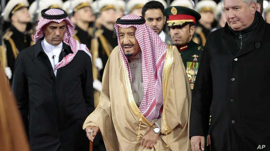 Saudi King Salman, center, and Russian Deputy Prime Minister Dmitry Rogozin, right, review the honor guard upon their arrival at Moscow's Vnukovo airport, Russia, Oct. 4, 2017.