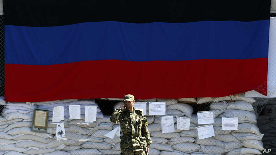 A pro-Russian gunman speaks by phone in front of the city hall decorated with the flag of self-proclaimed Donetsk People's Republic, in the center of Slovyansk, eastern Ukraine, May 8, 2014.