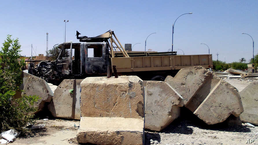 File - A  military truck damaged after clashes between Islamic State fighters and Iraqi security forces at a military base north of Baghdad.