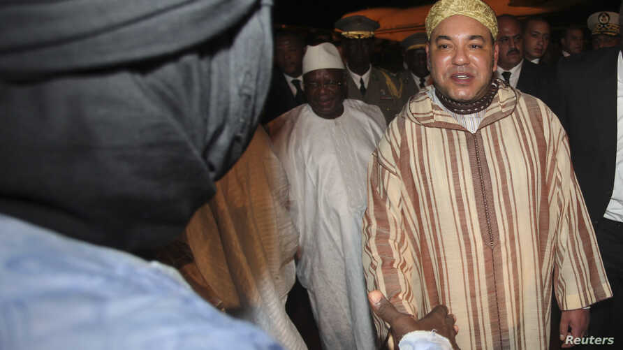 King Mohammed (R) of Morocco greets an unidentified person as he is welcomed by Mali's new President Ibrahim Boubacar Keita (C) at the Bamako-Senou International Airport September 18, 2013. REUTERS/Thierry Gouegnon (MALI - Tags: POLITICS ROYALS) - RT