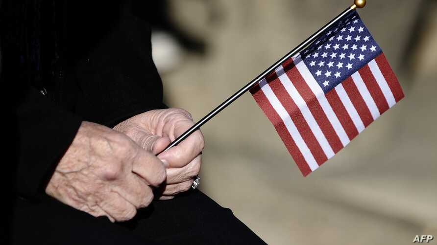 FILE - A woman holds a miniature US flag during a Veterans Day ceremony at Arlington National Cemetery in Arlington, Virginia.