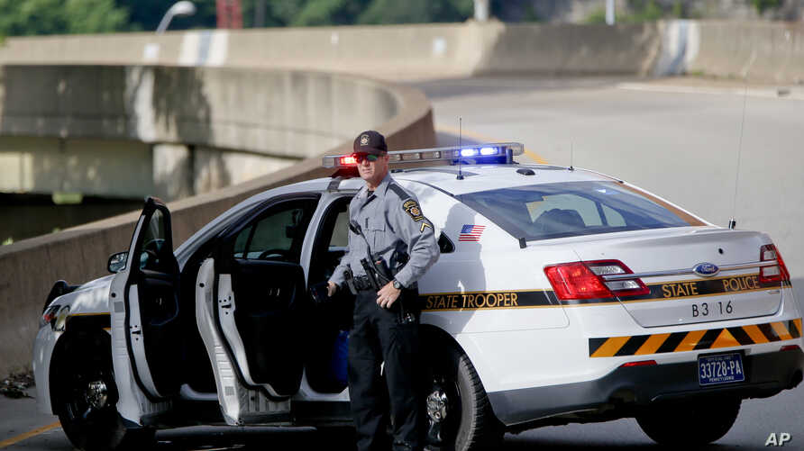 FILE - A Pennsylvania state trooper stands beside his vehicle parked on the entrance ramp to Interstate 376 out of Pittsburgh, June 26, 2018.