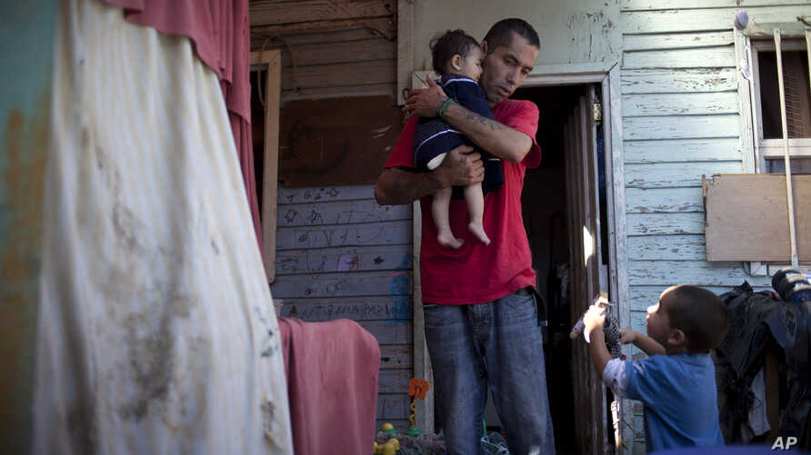 Ricardo Gonzalez holds her 8-month old daughter Keyla as his son Antonio, right, 3, talks to him at their home in the  Juan Pablo II shanty town in Santiago, Chile, Jan. 23, 2013.