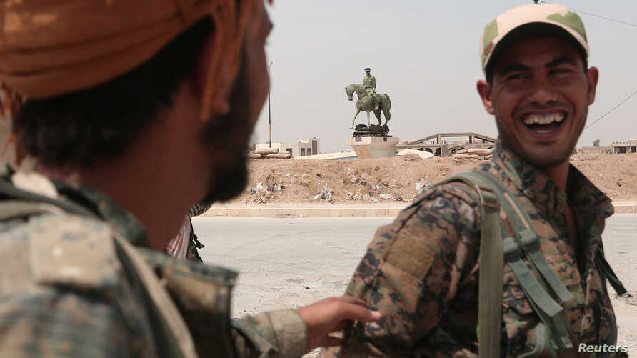 Kurdish fighters from the People's Protection Units (YPG) chat in the Ghwairan neighborhood of Hasaka, Syria, August 22, 2016. U.S. and Russian efforts to protect the local publation have allowed civilians to start returning to the city.
