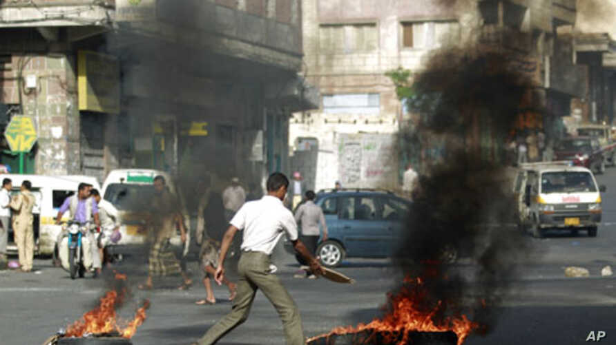 An anti-government protester burns tires during a protest to demand the ouster of Yemen's President Ali Abdullah Saleh in the southern city of Taiz, May 10, 2011