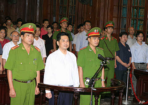 Cu Huy Ha Vu (C) stands between policemen in the dock during his trial at a court in Hanoi August 2, 21, 2011