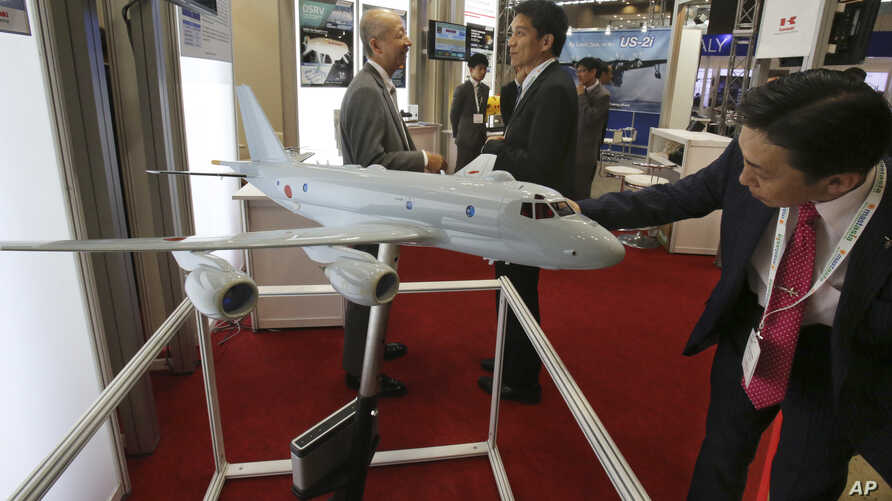 "A visitor looks at a miniature model of P-1 Maritime Patrol Aircraft of Kawasaki Heavy Industries, during "" MAST Asia"",  Japan's international arms exhibit, in Chiba, near Tokyo, June 12, 2017."
