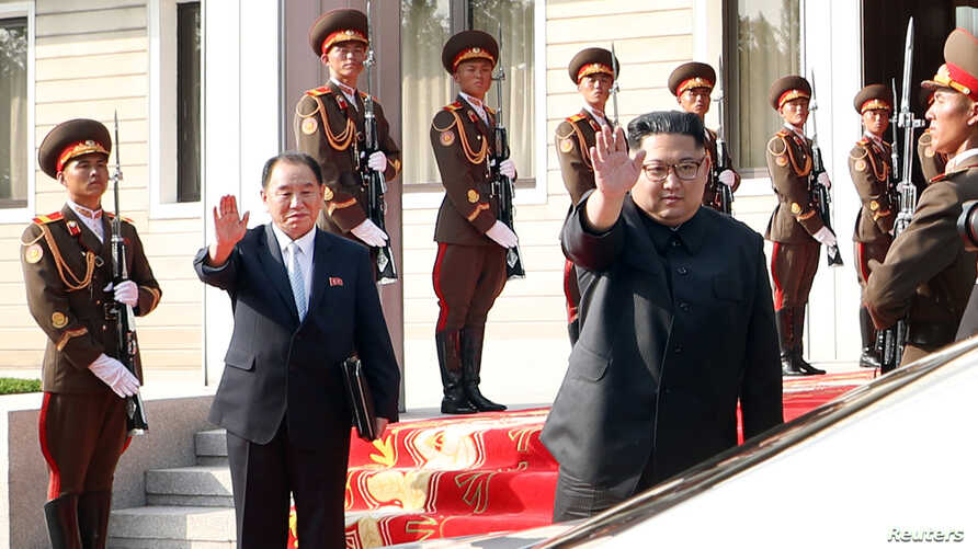 North Korean leader Kim Jong Un waves to South Korean President Moon Jae-in as they bid farewell after their summit at the truce village of Panmunjom, North Korea, May 26, 2018.