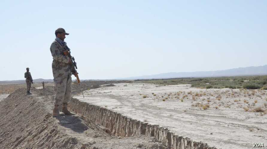 Pakistani soldiers stand guard near the trench near the Afghanistan border.