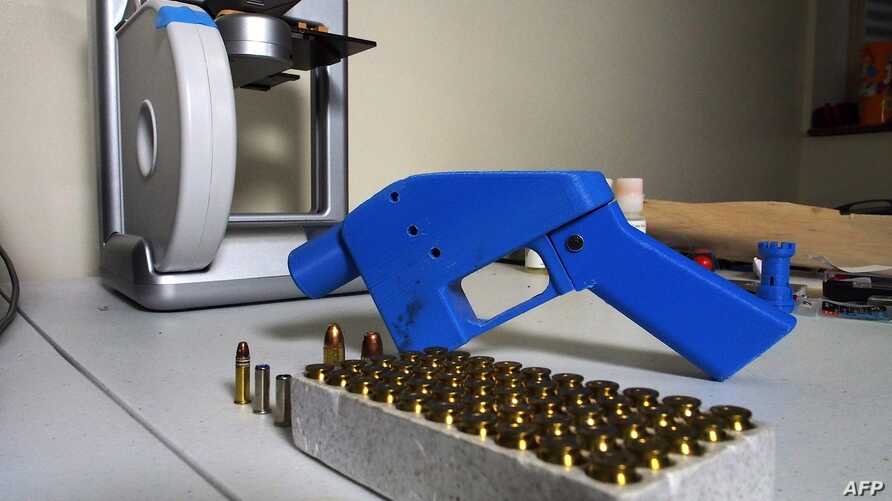FILE - A Liberator pistol is seen next to the 3D printer on which its components were made, July 11, 2013.