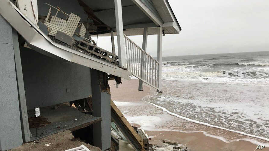 In this Jan. 3, 2018 photo, an unoccupied beachfront home collapses due to beach erosion in Ponte Vedra Beach, Florida. No one was injured. Several homes along the northeast Florida coast collapsed during Hurricane Irma in September.