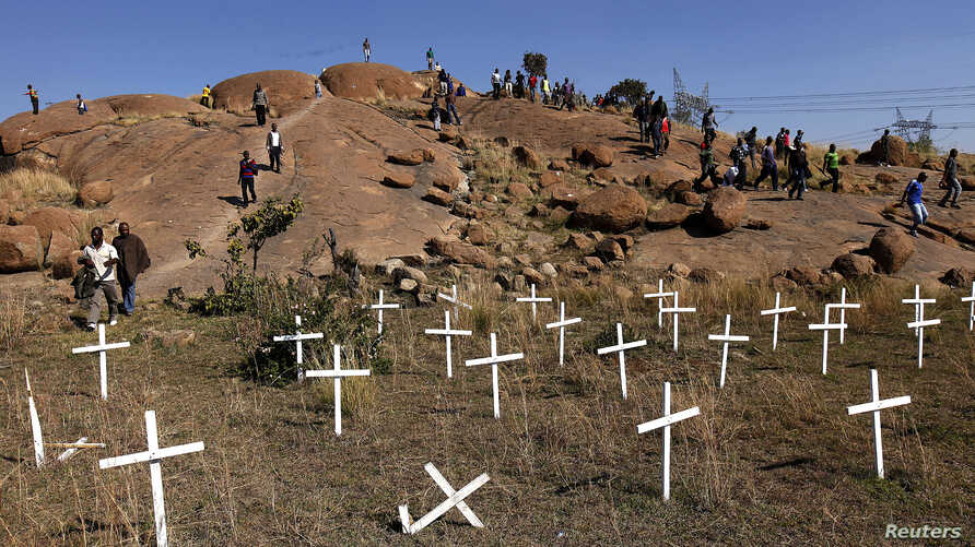 "Members of South Africa's mining community walk near crosses placed at a hill known as the ""Hill of Horror"", where 43 miners died during clashes with police last year at Lonmin's Marikana platinum mine in Rustenburg, northwest of Johannesburg, May 14"