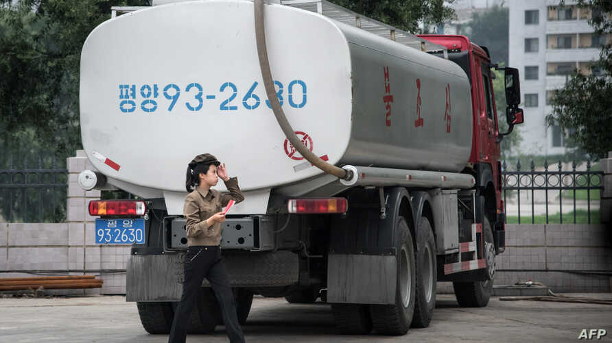 FILE- In this photo taken on July 21, 2017, a petrol station worker walks past a fuel truck in Pyongyang.