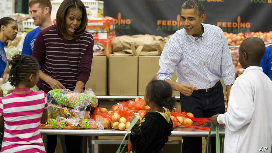 President Barack Obama, right, and first lady Michelle Obama participate in a Thanksgiving service project by handing out food at the Capital Area Food Bank in Washington, Nov. 27, 2013.
