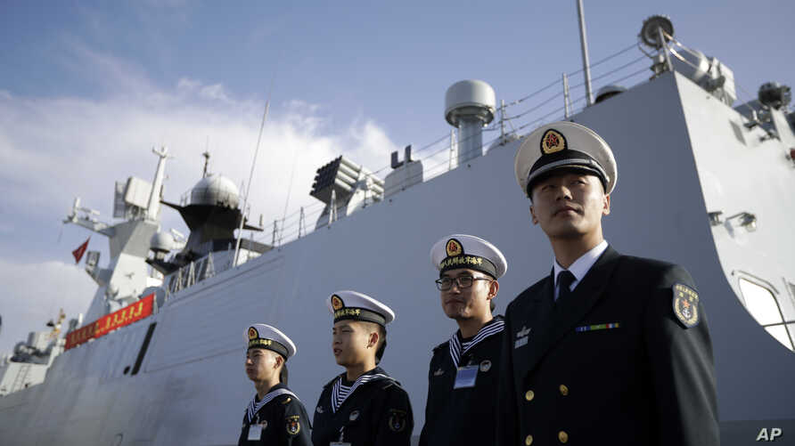 FILE - Chinese Navy officials stand in front of the ship Daqing.