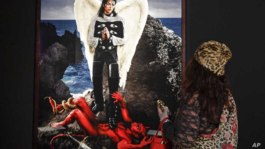 A visitor watches the picture 'Archangel Michael: And no message could have been any clearer' from US artist David LaChapelle at a preview of the exhibition 'Michael Jackson: On The Wall' at the Bundeskunsthalle museum in Bonn, Germany, March 21, 201