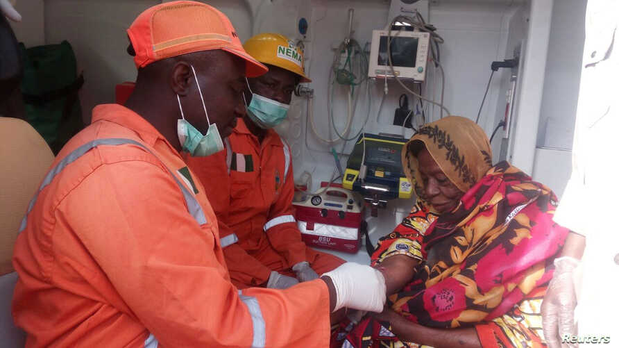 National Emergency Management Agency workers attend to a woman after suicide bombers detonated their explosives in Maiduguri, Nigeria, March 15, 2017.