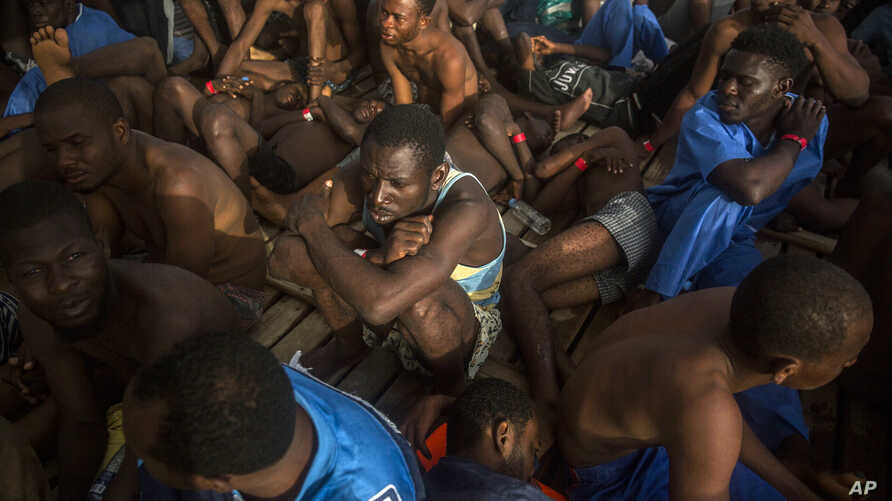 Migrants sit on the deck of the vessel of Proactiva Open Arms after being rescued in the Mediterranean Sea, about 15 miles north of Sabratha, Libya on July 25, 2017.
