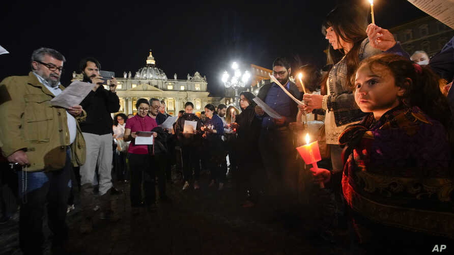 People hold candles as they attend a prayer vigil for terminally ill toddler Alfie Evans, in St. Peter's Square at the Vatican, Thursday, April 26, 2018.