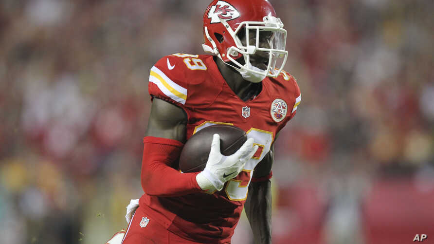 Kansas City Chiefs free safety Husain Abdullah carries the ball after intercepting a pass and running it back 39 yards for a touchdown during the fourth quarter of an NFL football game against the New England Patriots, Sept. 29, 2014.