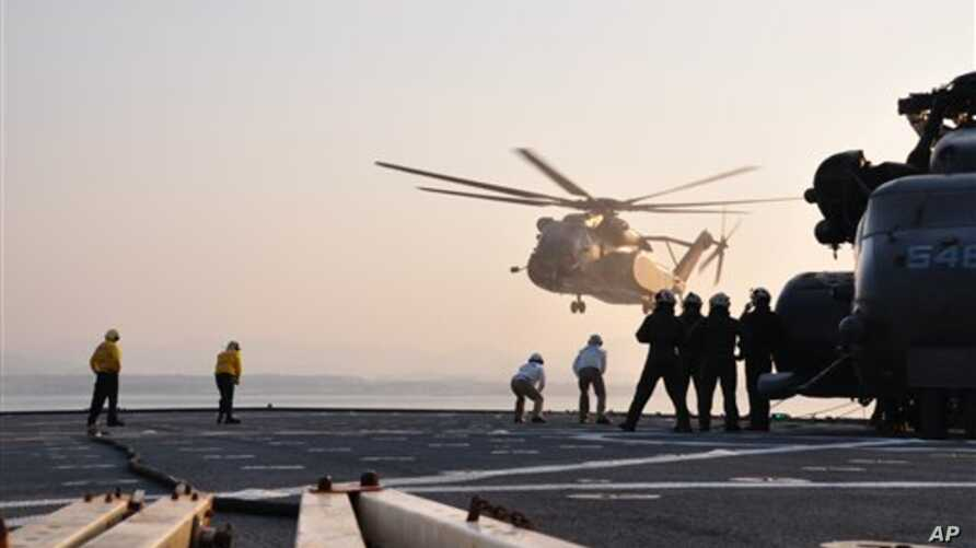 MH-53 helicopters land aboard the amphibious dock landing ship USS Tortuga (LSD 46) in the Sea of Japan, March 12, 2011