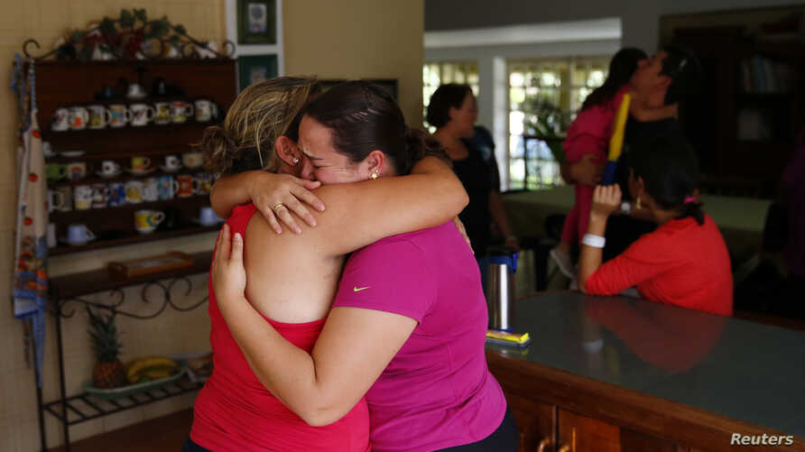 FILE - Natalie Pereira, center, cries as she embraces her sister-in-law before her move to the U.S. after winning the green card lottery, at their home in Valencia, Venezuela, April 6, 2014.